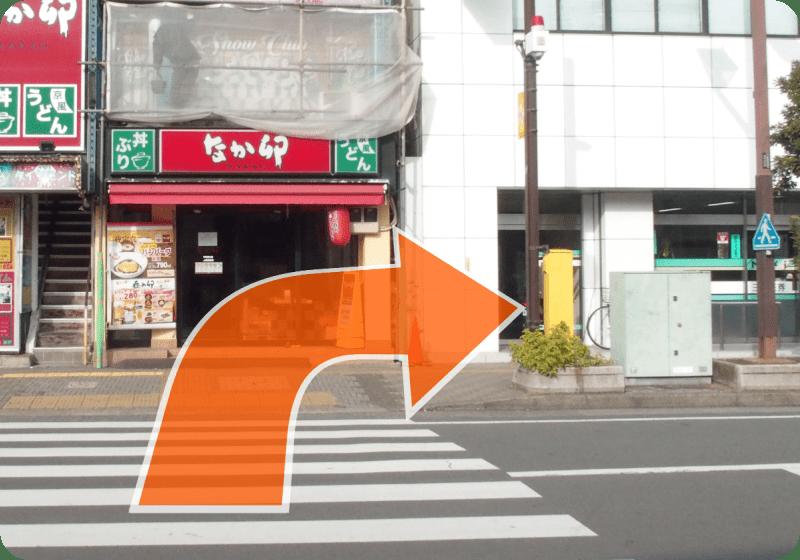 階段を降りてすぐの横断歩道を渡り、右に曲がってください。