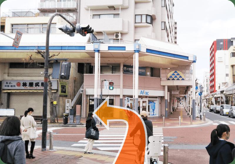 信号のある横断歩道を渡り、渡った先のビル(Afracのビル)にある階段に向かいます。